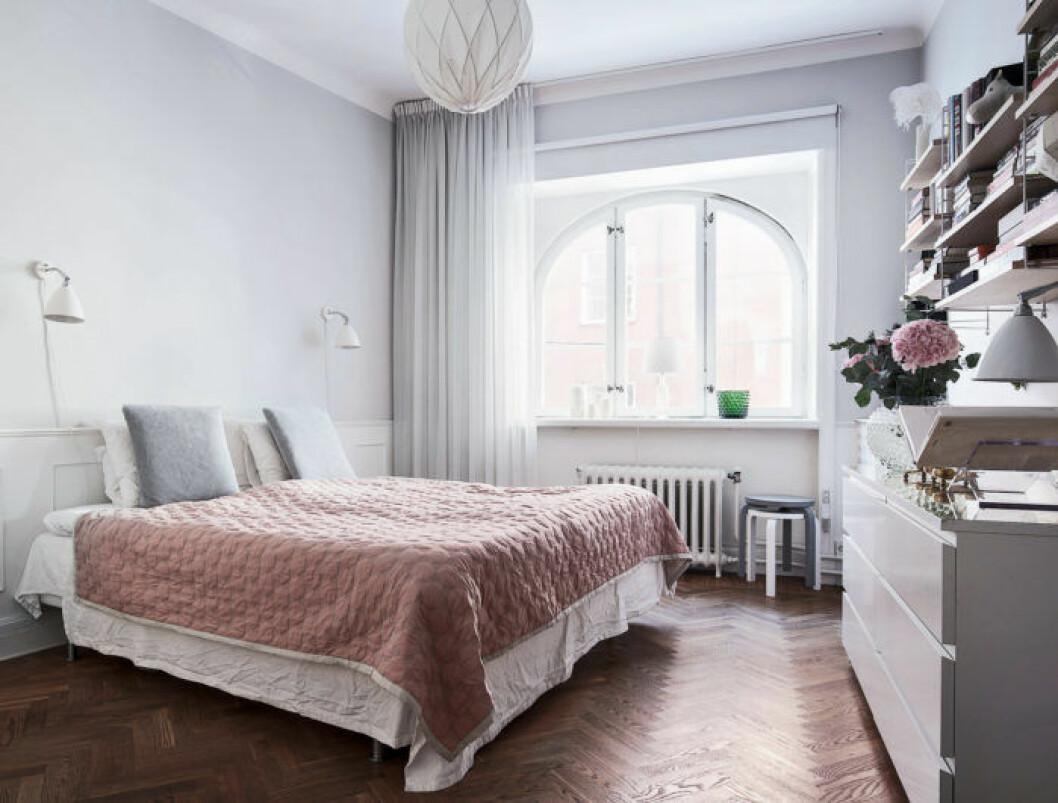 Ljust sovrum med en säng i mitten som har ett rosa överkast