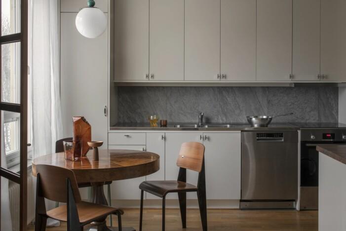 Kök med lackade köksluckor i Kvänums kulör Ax och ett matbord med stolar av Jean Prouvé.