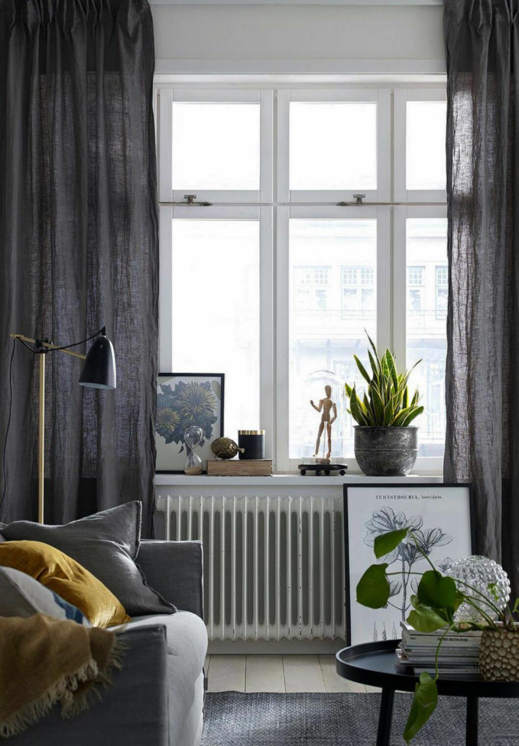 Mörkgråa gardiner som ramar in fönstret