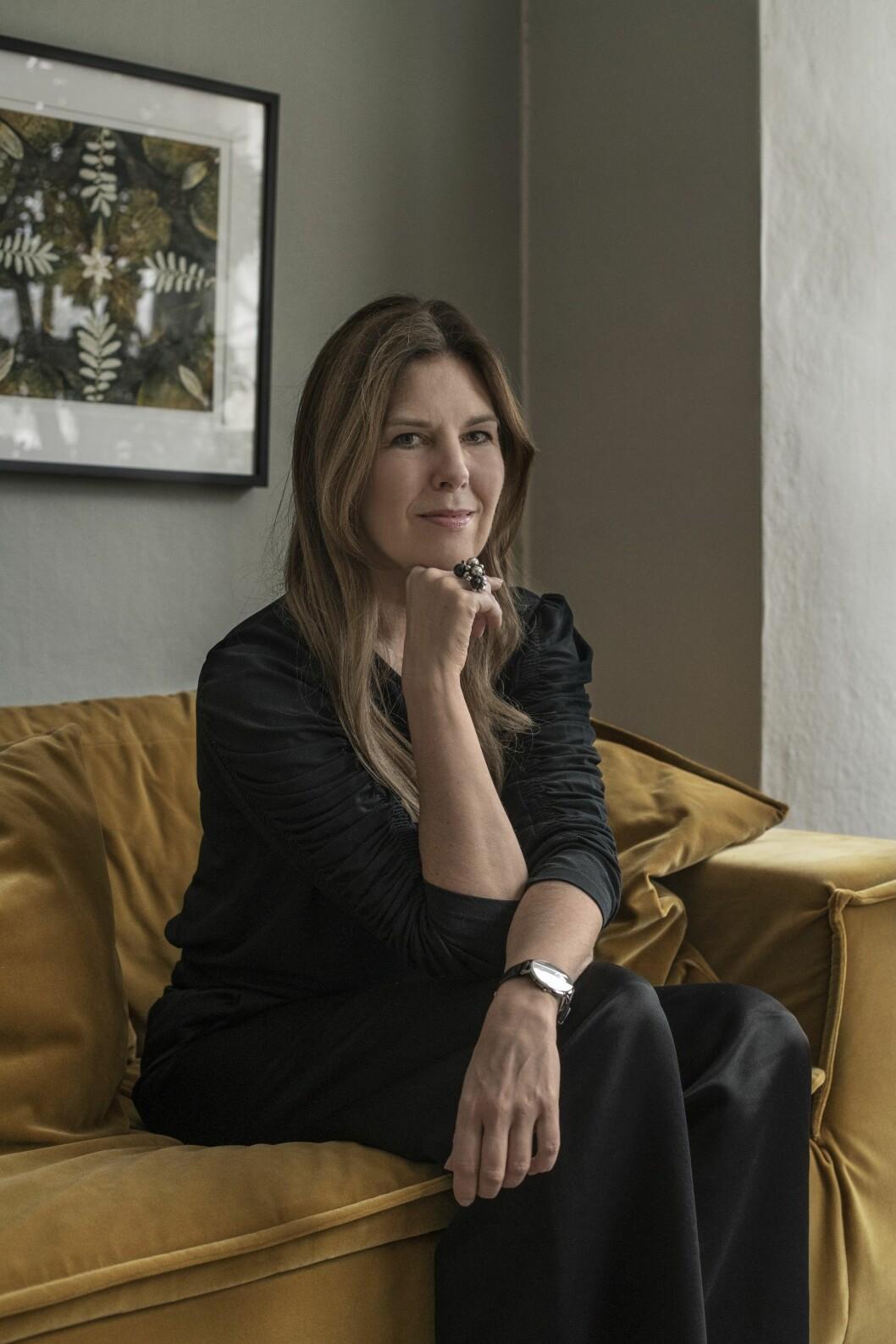 Karin Sköldberg i svart dress på den gula soffan i vardagsrummet.