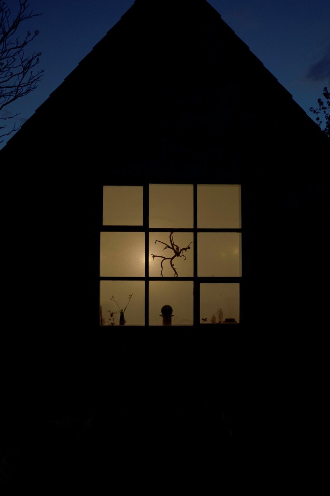 Ett upplyst fönster till huset.