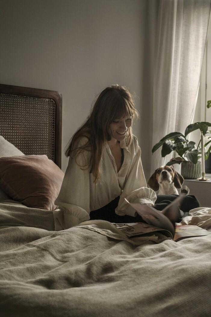 Modefotografen Sara Bille sittandes i sitt sovrum