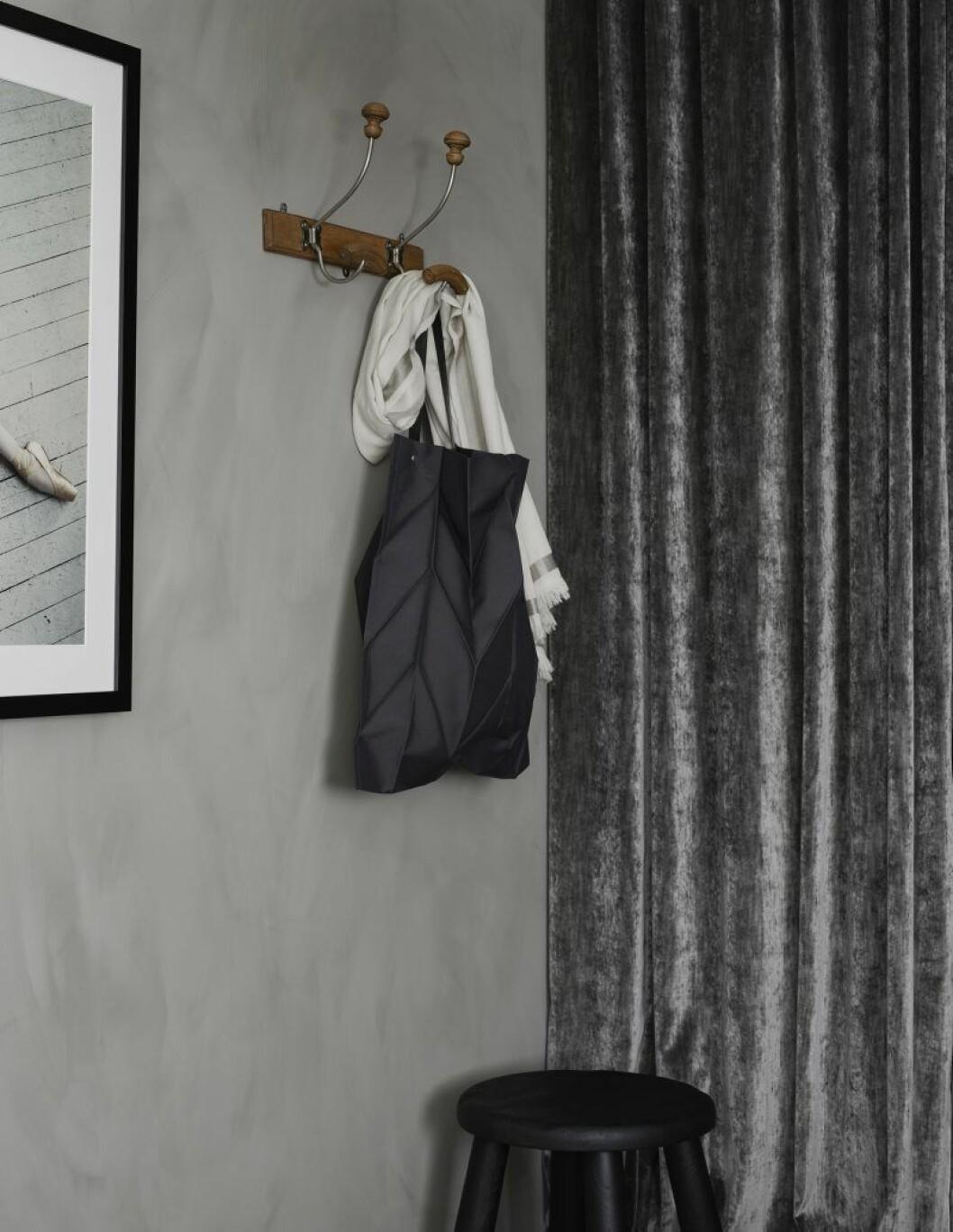 Grå kalkfärg kombineras med en sammetsgardin i sovrummet.