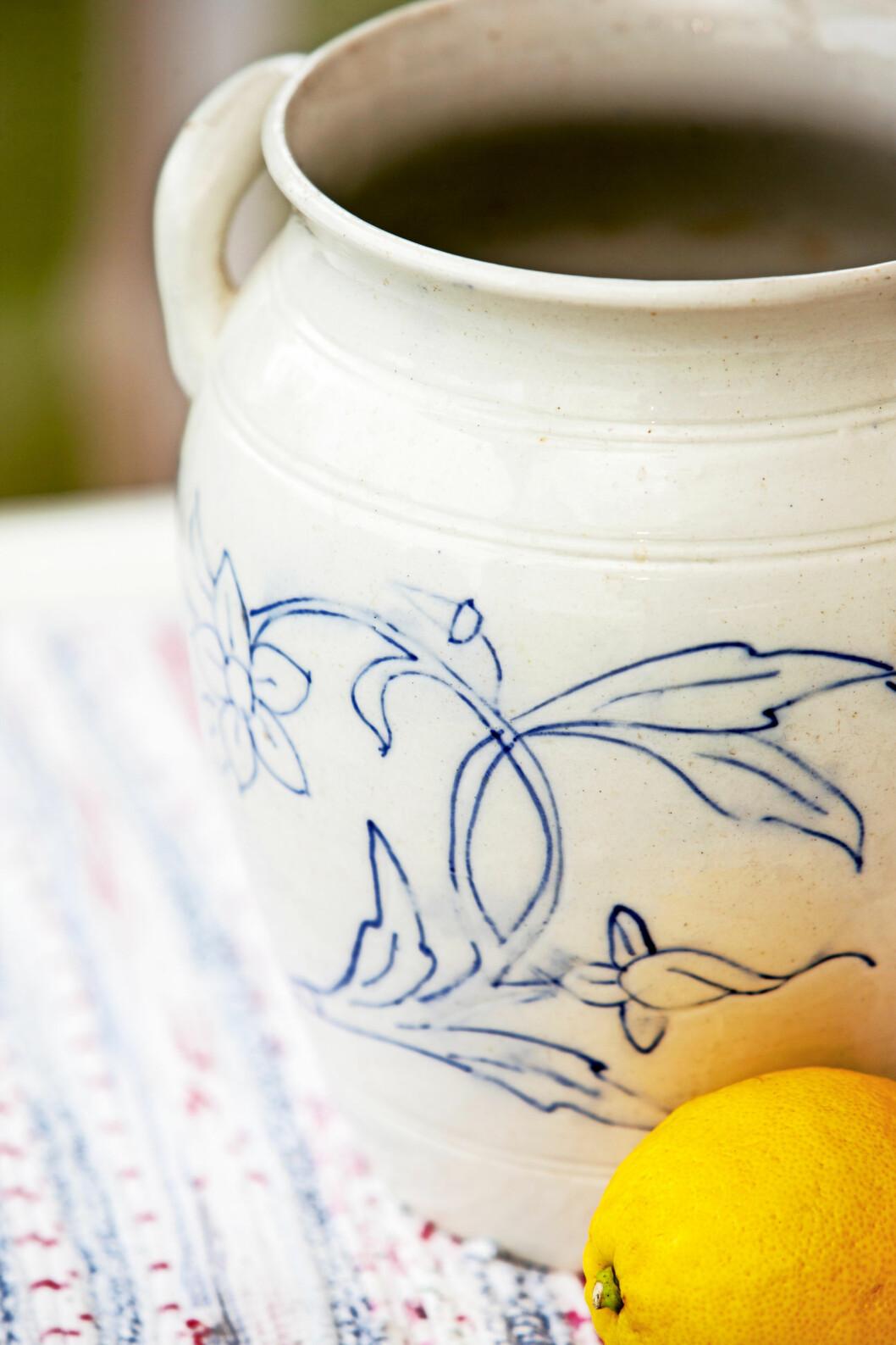 Gräddvitt krus med blått mönster. I förgrunden syns en citron.