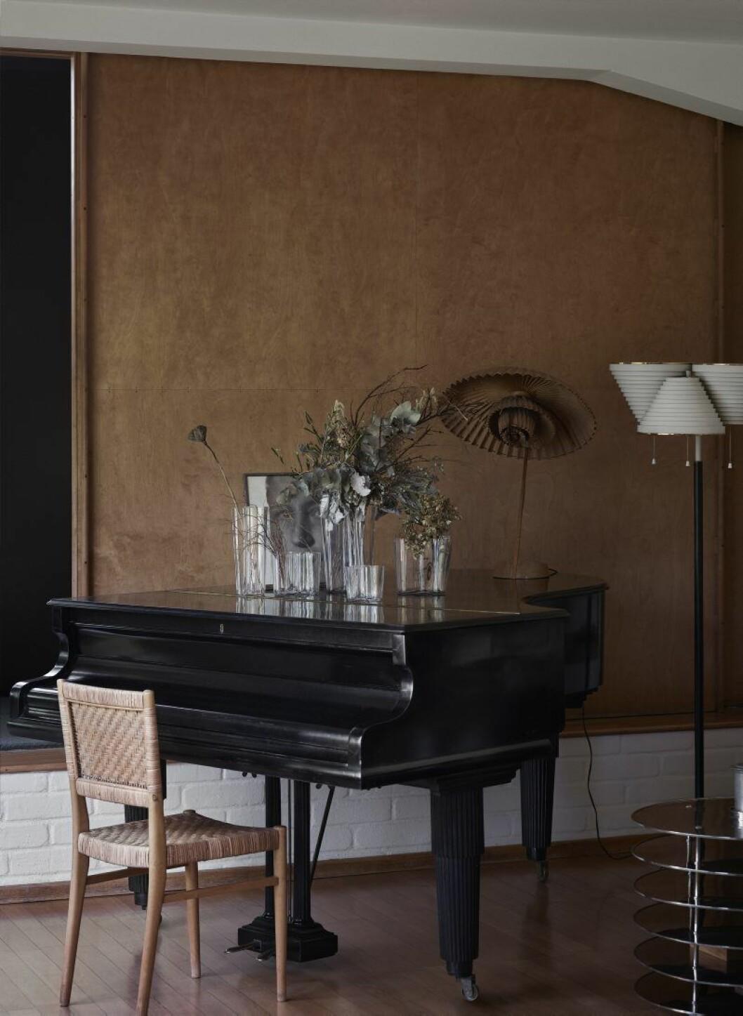 Vardagsrummet med vasen Savoy i olika storlekar på flygeln, alla Iittala. Bredvid pianot golvlampa A809, Artek. På pianot ett porträtt av Aino och en lampa av Poul Henningsen. Pianostol, Aalto. Bordet är en prototyp från 1929.