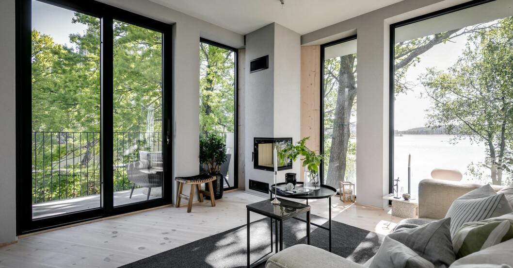 Vardagsrum med stora fönsterpartier i två väderstreck.