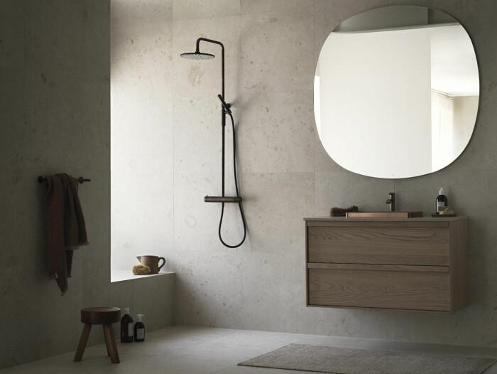 badrum i kalksten och trä med stor rund spegel