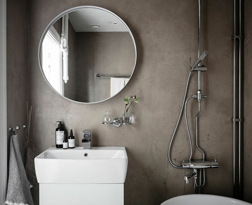 Stor rund spegel i snyggt litet badrum