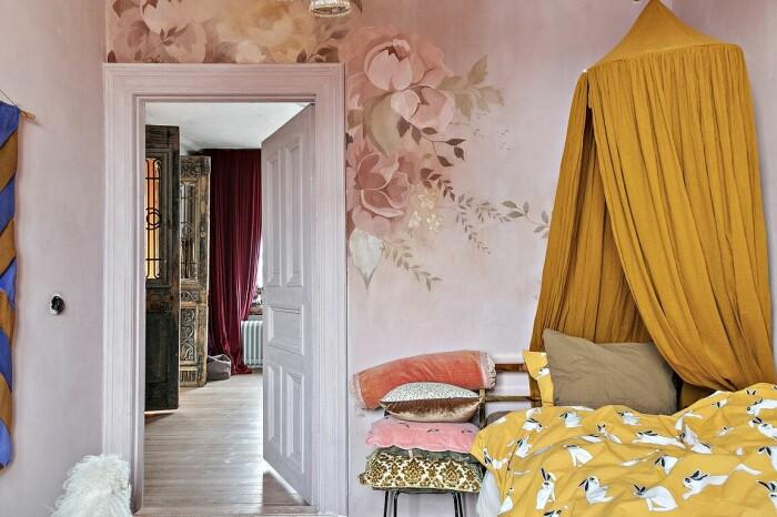 barnrum med väggmålning i rosa och gult