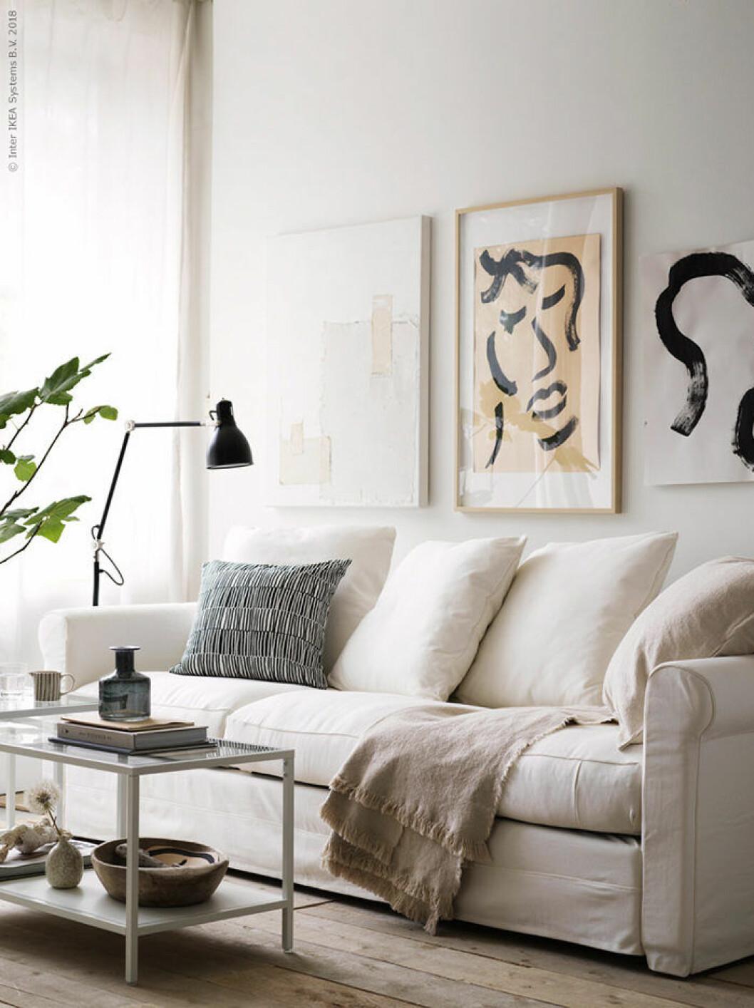 En golvlampa vid soffan i vardagsrummet lyser upp, här hos Ikea