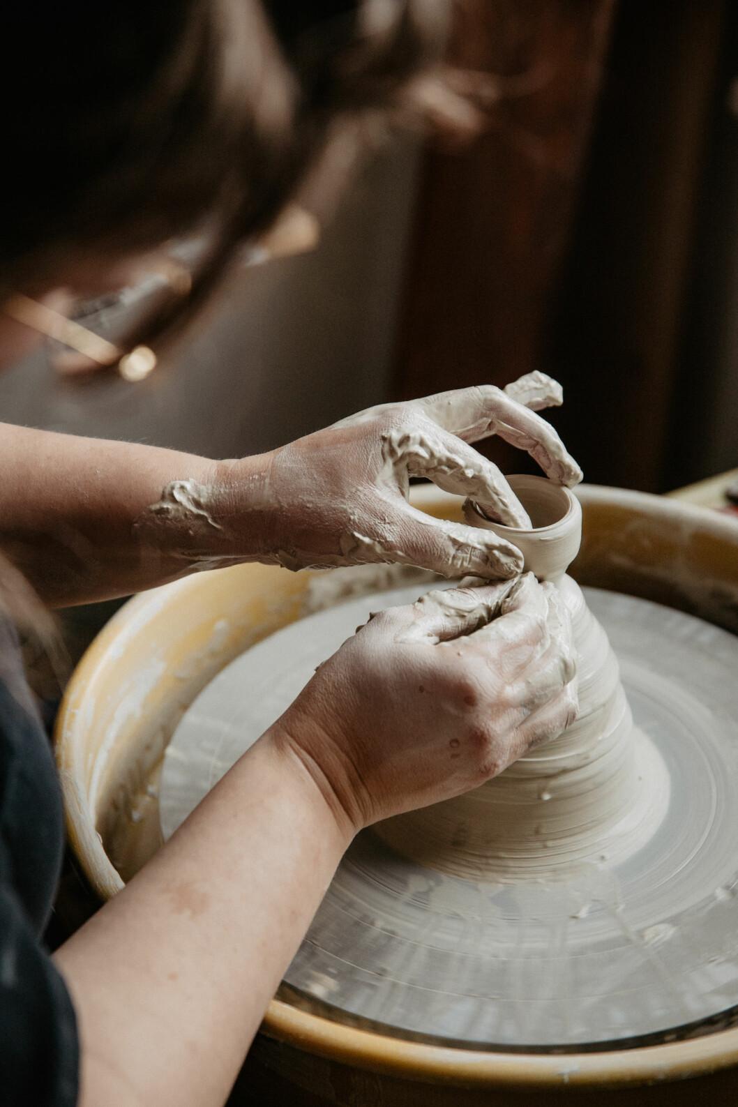 Händer som drejar lera på en drejplatta.