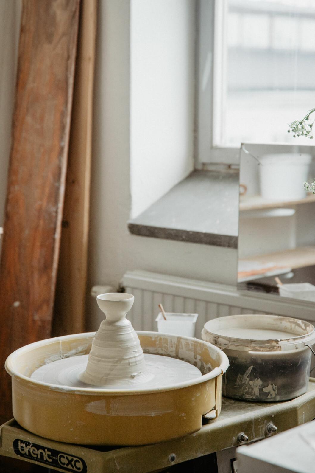 En ateljé med en drejplatta och början på ett keramikobjekt.