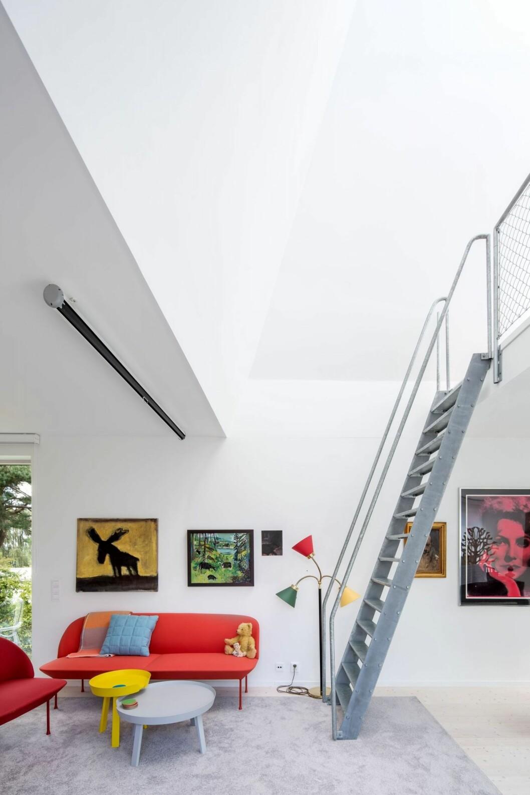 Vitt rum med röd soffa och färgglada tavlor.