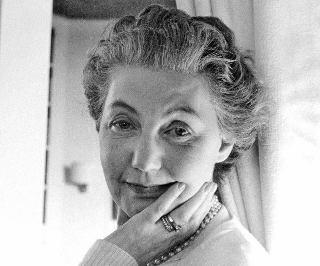 Närbild på en leende Estrid Ericson med handen under hakan, arkivbild från 1957