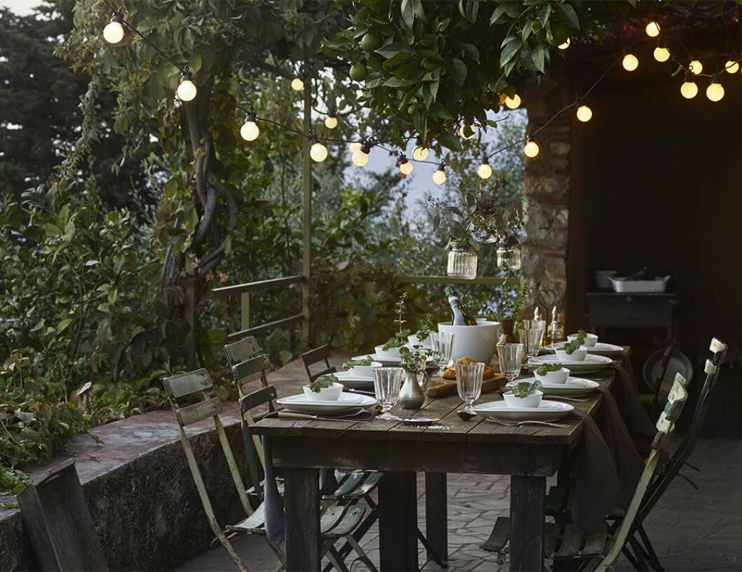 Uteplats med matbord och ljusslingor