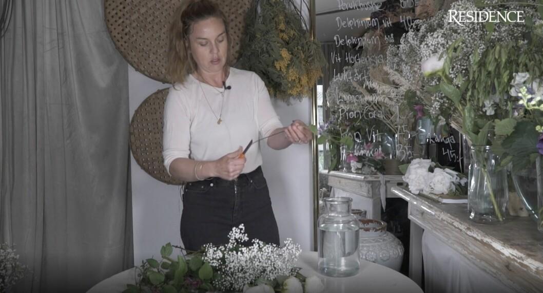 Floristen Sandra snittar blommorna.