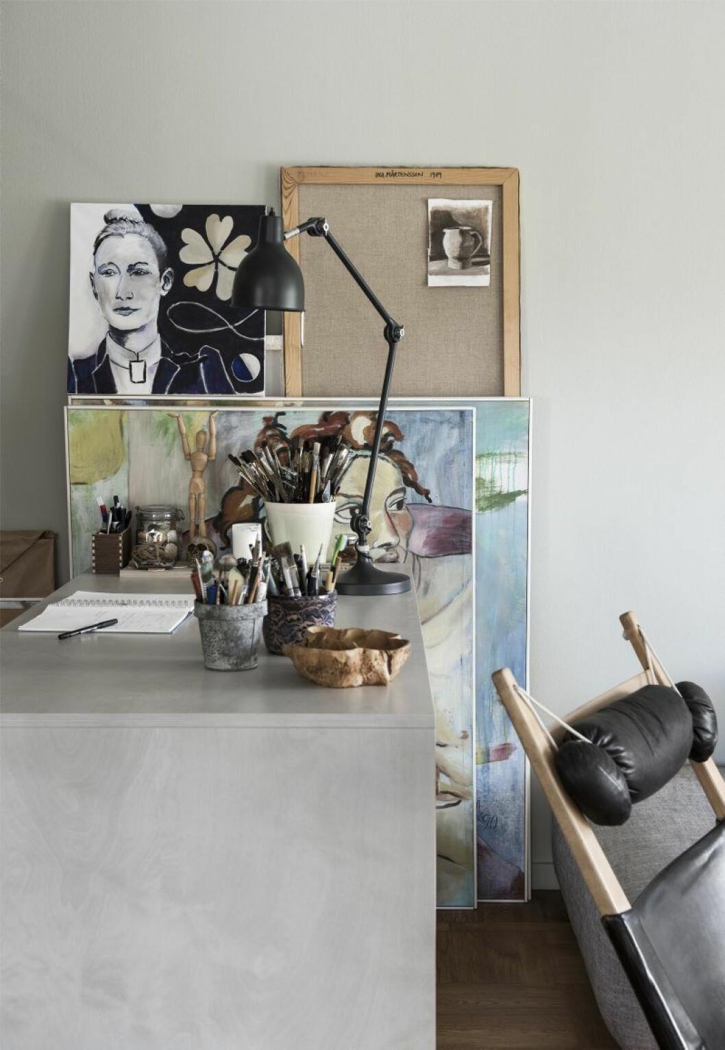 Verken av Ina M Andersson. Ateljédelen är inkilad i ett hörn av vardagsrummet. I familjen Anderssons fritidshus i Strängnäs finns en mer tilltagen arbetsyta.