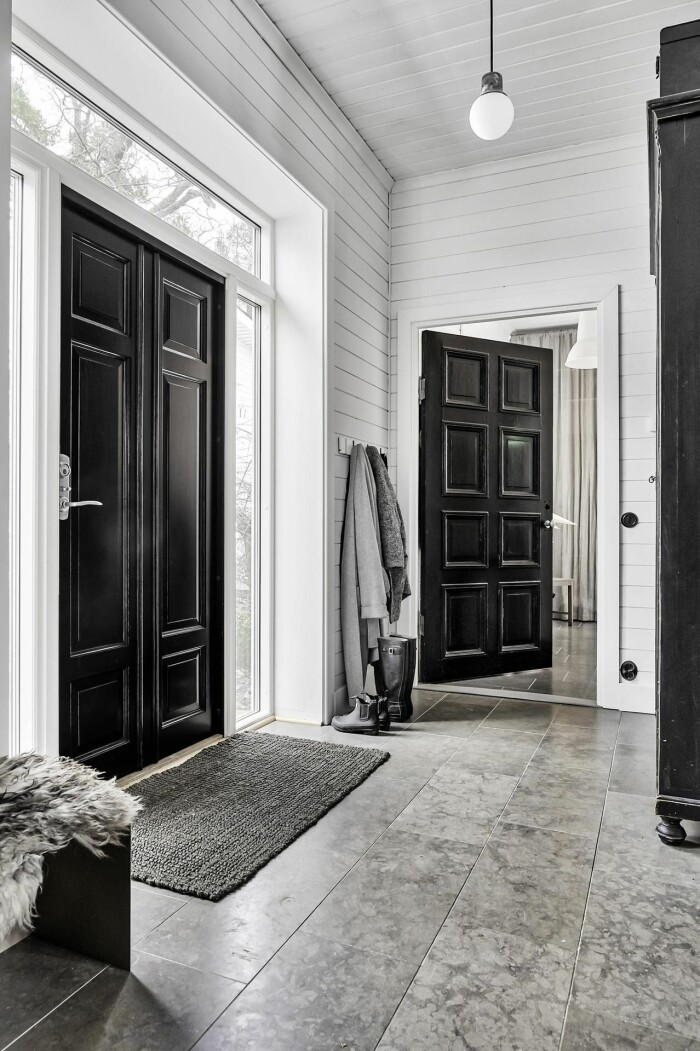 hall med svarta dörrar och vita väggar