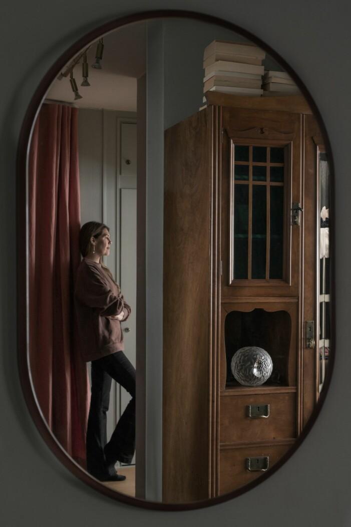 I en oval spegeln från Montana syns Karin Sköldberg stå lutad mot väggen. Vi ser hennes morfars skåp och ett draperi från Astrid.
