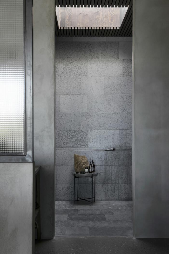 Badrum i kalksten där både vatten och ljus faller ovanifrån. Bord från H Skjalm P.