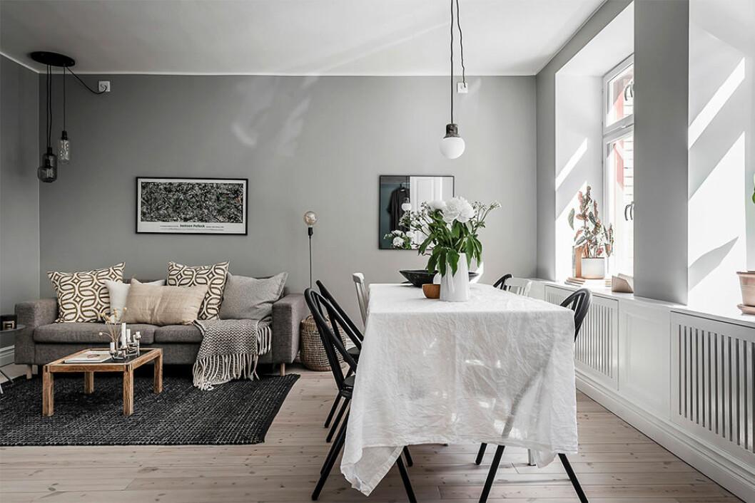 Snyggt vardagsrum i liten bostad med soffhörna och stor matplats
