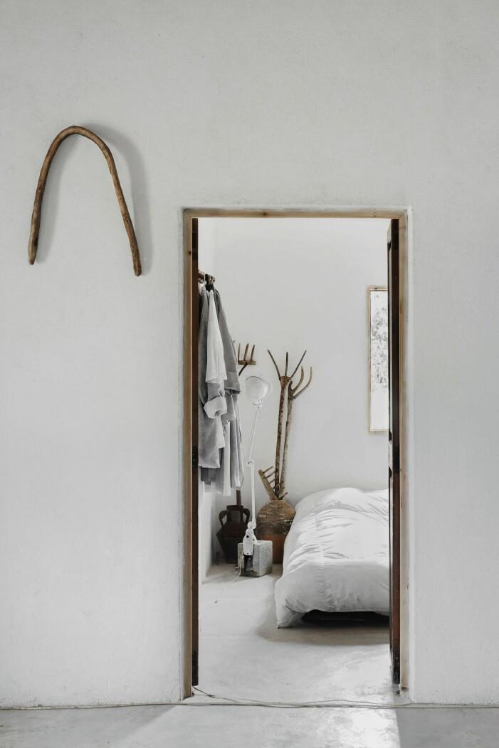 Inblick in i vitt avskalat sovrum genom dörröppning