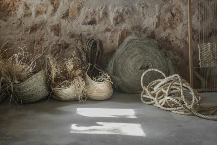 Korgar fyllda med strå, snöre, träbitar och ull som kanske blir konst eller kläder.