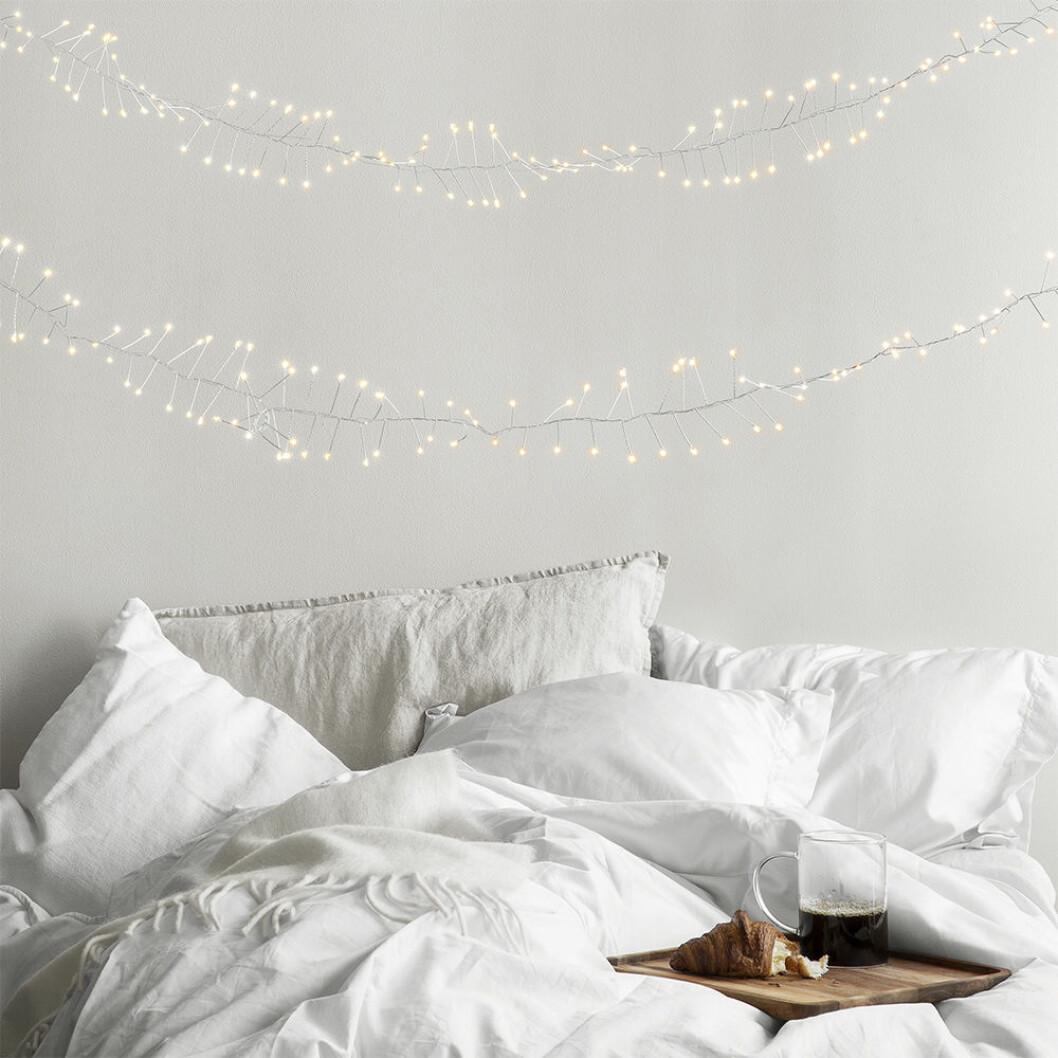 Avskalat sovrum med ljusslingor som ger julkänsla
