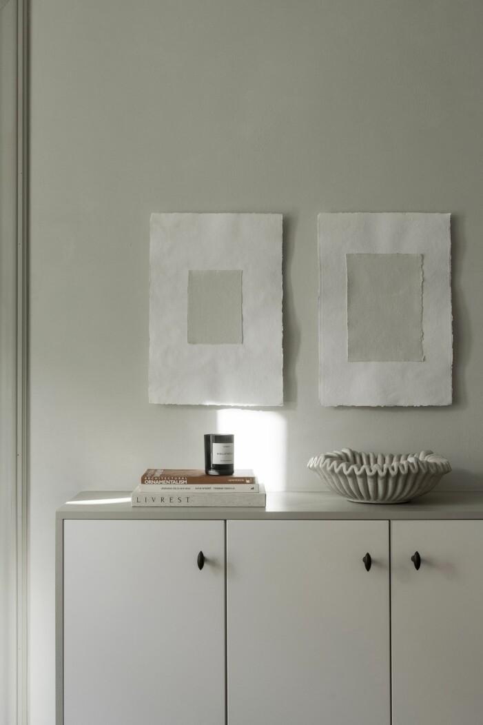 Tavlor gjorda av Lovisa Häger och skål av marmor ovanpå skåp