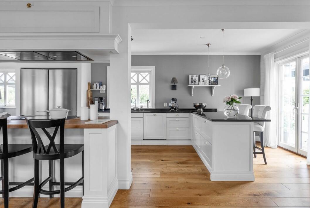Fräscht kök med köksö och barbord.