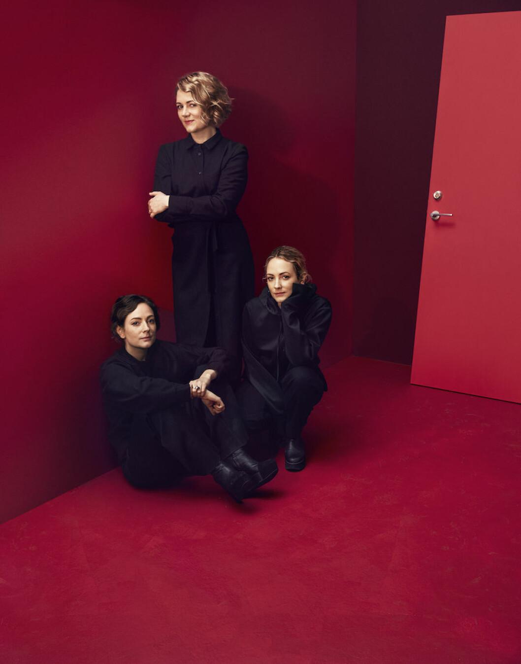 Systrarna bakom designvarumärket Minimarket fotade tillsammans i ett rött rum.