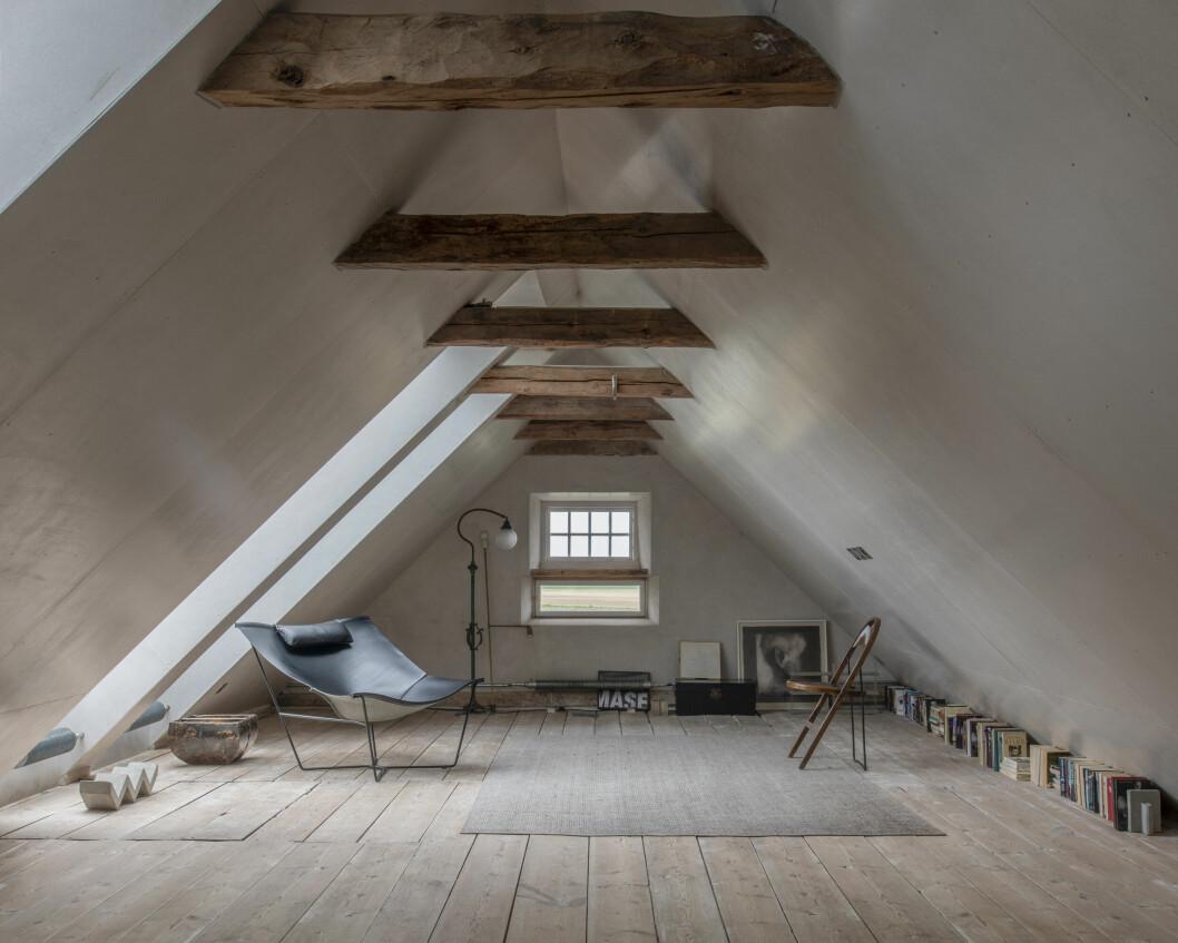Vindsvåning med synliga takbjälkar och flera objekt, bland annat stolar, tillhörande dramatikern Lars Norén.