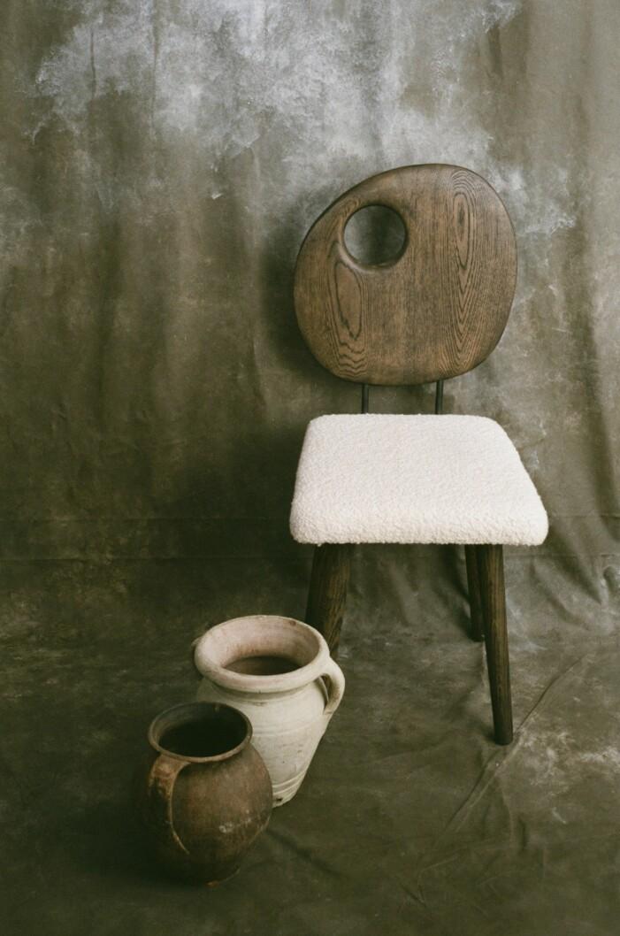 Mörk stol med fårskinnsits.