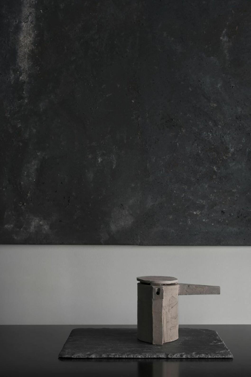 Tekanna i cement på skifferplatta. Konst av Robin Klang. Vas Mama, Ilse Crawford för Georg Jensen. Färg på väggen Jotun. Hållare i mässing för rökelse, Cinnamon projects, säljs via Perspective Studio.