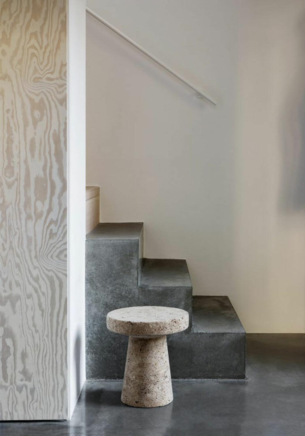 Den varma grå nyansen på betongen i kombination med plywooden gör att det nyrenoverade huset känns varmt och välkomnande.