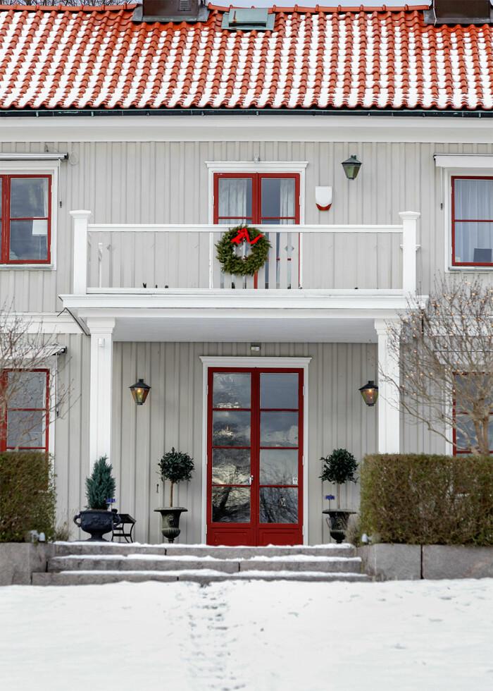 hus med röda fönsterkarmar och en röd dörr