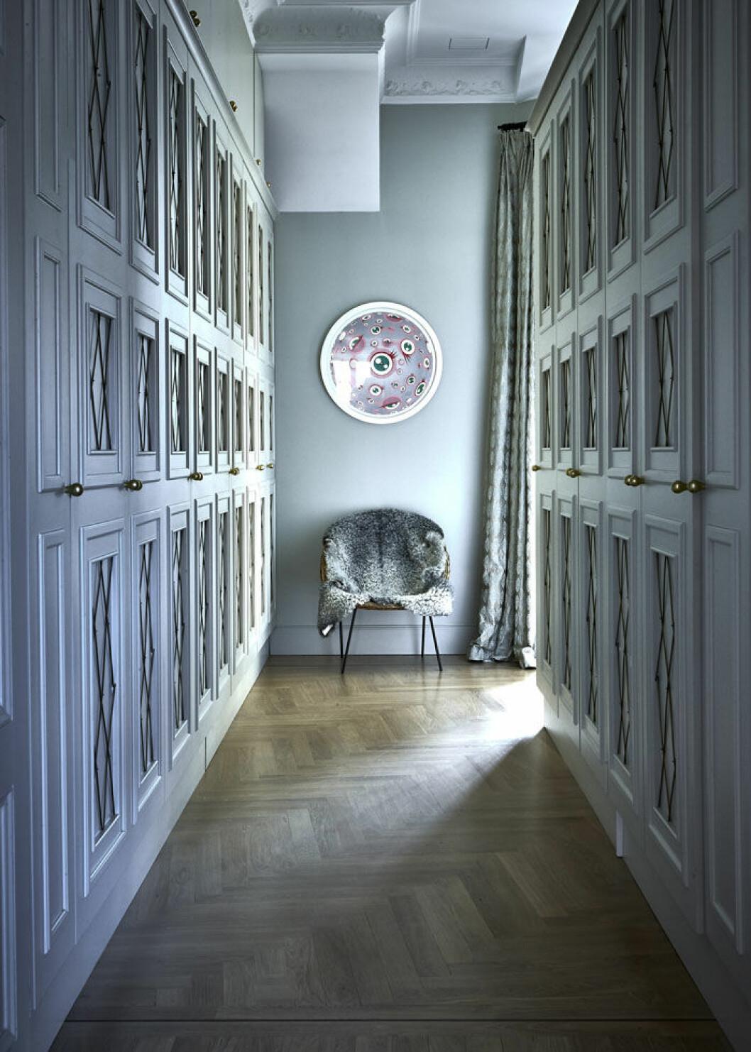Nathalies walk-in closet har ritats av arkitekten Olle Rex med ett tiotal platsbyggda skåp, vart ett och välfyllt med designerplagg. Konst på väggen, Takashi Murakami. Fåtöljen är ett fynd från Bukowskis market.