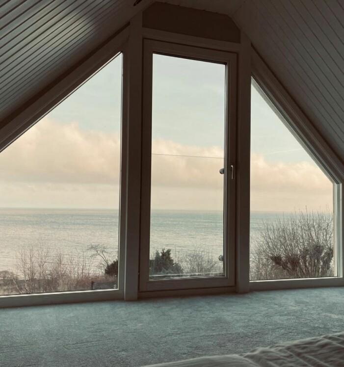 Måns Zelmerlöw och Ciaras sovrum efter renoveringen stora fönster från golv till tak som nu släpper in havet i rummet.