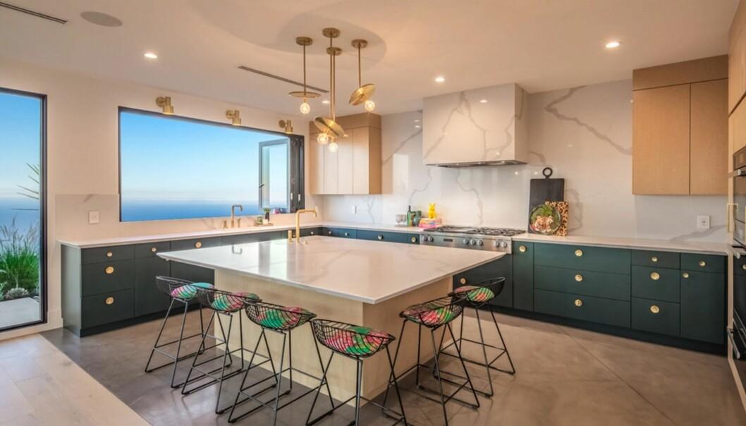 Köket med detaljer i marmor och trendigt gröna köksluckor.
