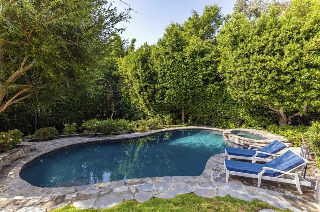 Avslappnat poolområde med pooler i två storlekar och vacker stenläggning som smälter in med naturen.