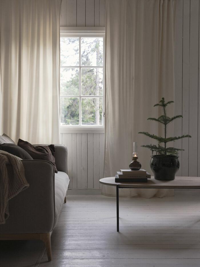 skandinaviskt avskalat och minimalistisk vardagsrum med liten julgran