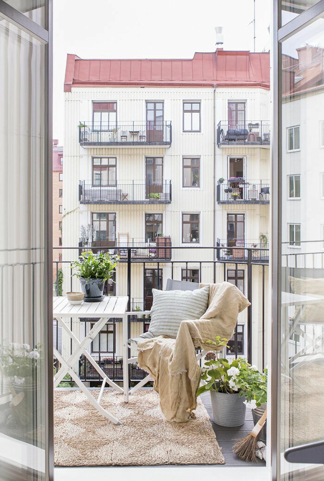 Skandinaviskt inredd balkong med naturnära färger och matta på balkongen