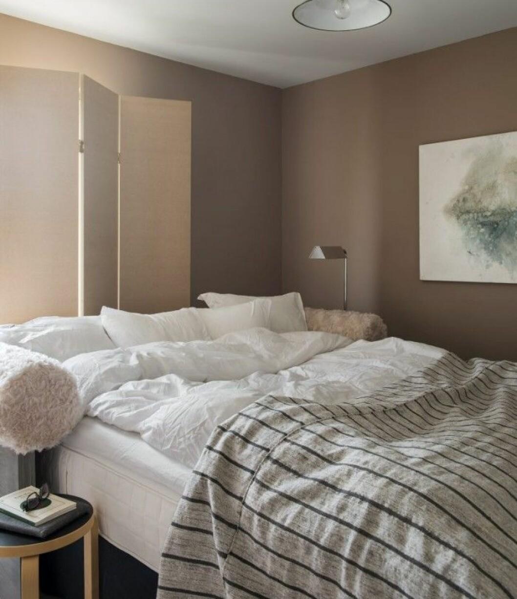 I sovrummet råder asketiskt lugn med lite lurv på sänggaveln. Säng och vikskärm är i egen design. Lampor inropade på auktion. Överkastet är en Kelimmatta.