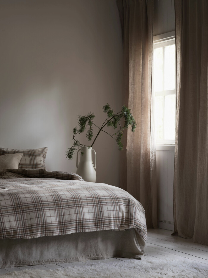 Sovrum med rutiga påslakan och tuftad matta