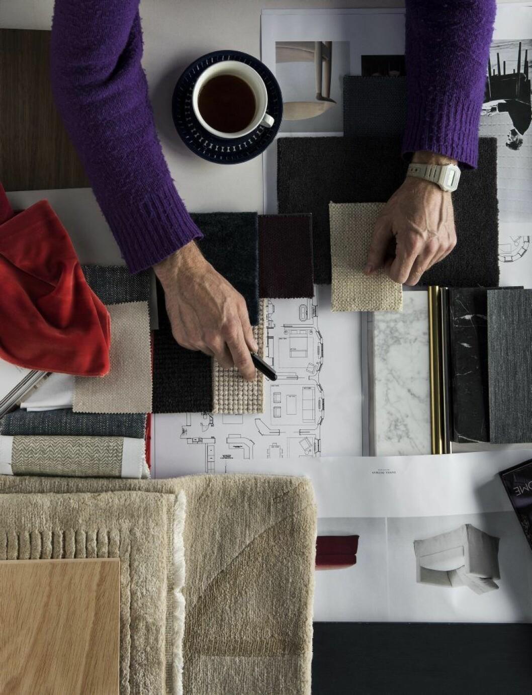 En inredare at work. Textilprover, skisser och en kopp kaffe. Men det mesta arbetet sker i alla fall på plats, »när man flyttar runt grejorna«.