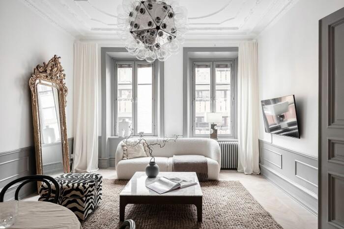 vardagsrum i sekelskifteslägenhet med spegel med guldram och grå paneler samt kvistar i kruka