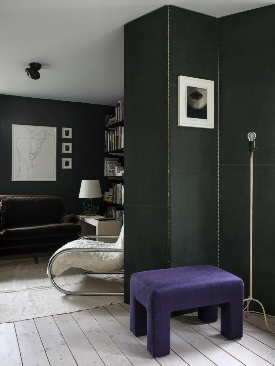 Egen textilklädd och målad vikskärm. Den lila pallen är ritad av den amerikanske möbeldesignern Milo Baughman, en av Daniels favoriter. Foto på skärm, Strömholm. Omklädd 70-talsfåtölj, sidobord i egen design, bordslampa, Jean-Michel Frank. Konst i bibliotek, Andy Warhol.