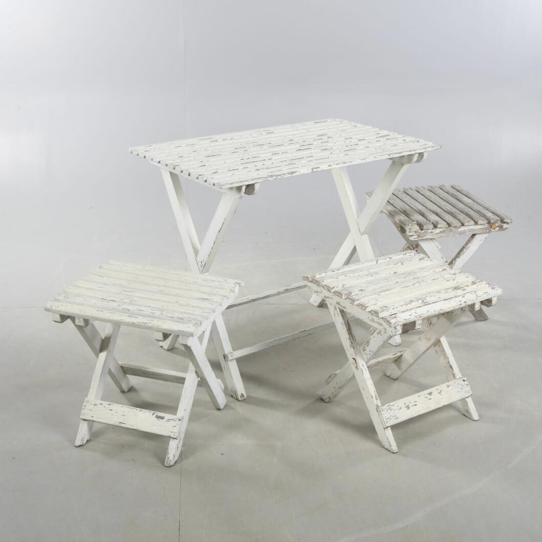 Bord och tre stolar utan ryggstöd i slitet vitt trä.