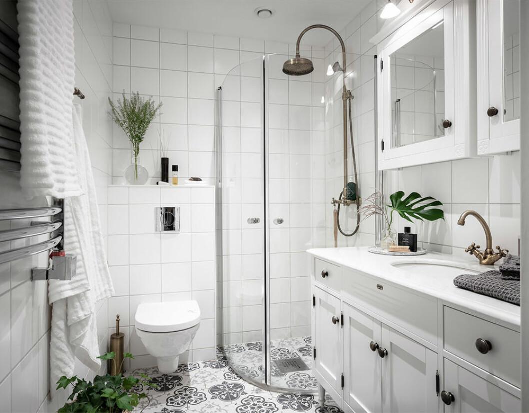 Badrum med mönstrat kakelgolv och gröna växter