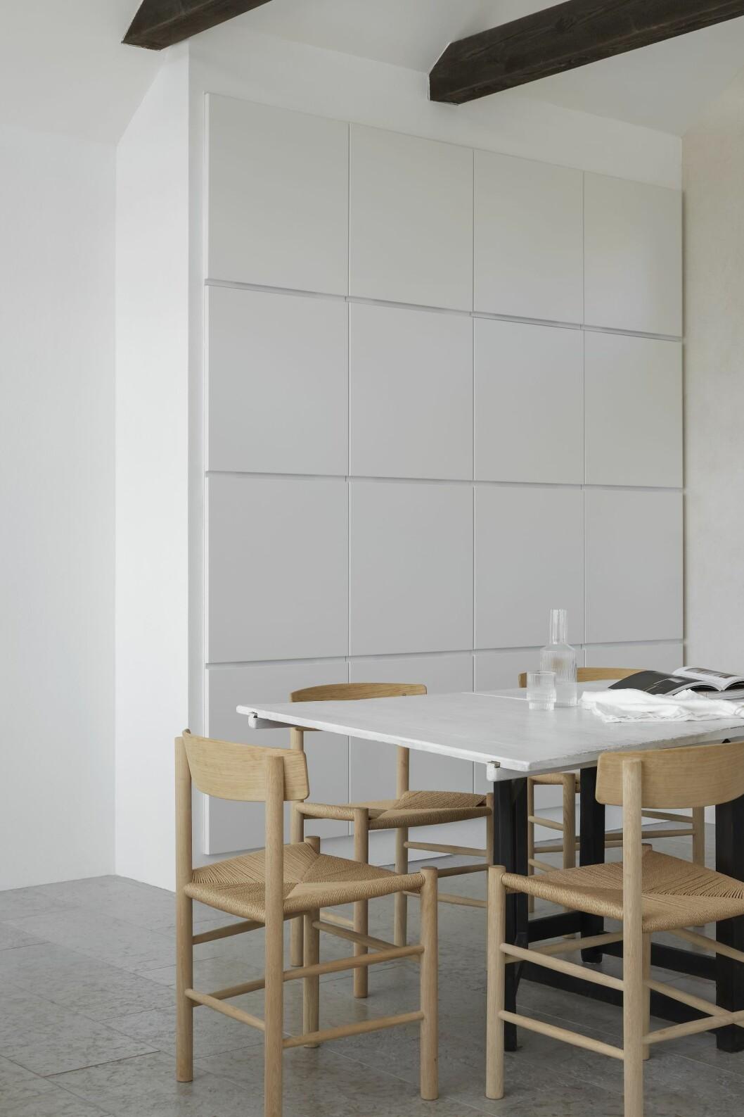 Fyra garderober från Kvik vid matplatsen. Vitmålat matbord, antikt. Stolar J39 ritade av Børge Mogensen, Fredericia. Kanna och glas från Ferm Living.